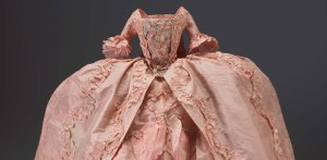 Doll's dress, 18th century. Doll's dress, pink silk taffeta, in two parts. (Modern stand and wire support for skirt). The Elizabeth Day McCormick Collection.